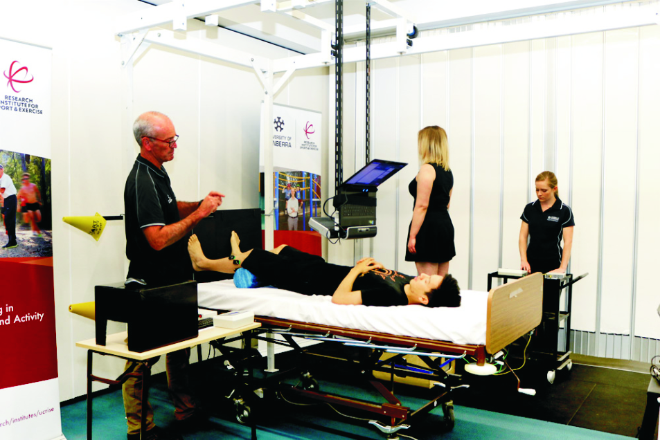 Professor Gordon Waddington (left) and Honours student Ashleigh Marchant (right) work with research volunteers on their proprioception study, performing a series of exercises standing and lying down. Photo: Vanessa Lam